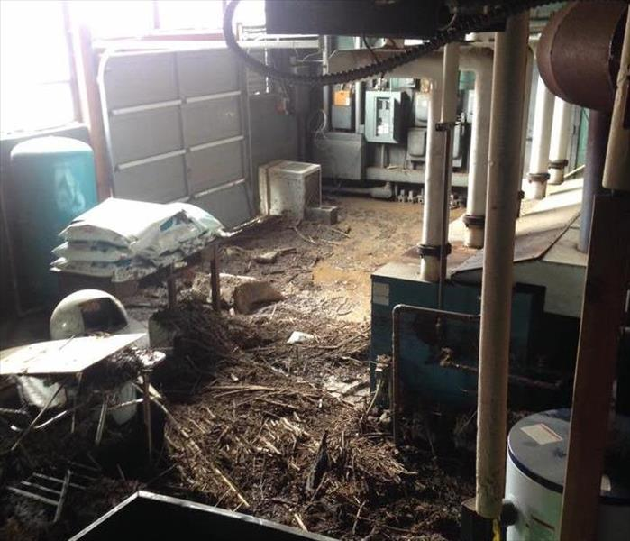 Garage floor covered in mud and debris from local flooding