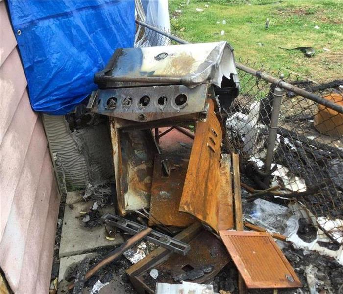 A grill caught fire and scorched the side of this home.