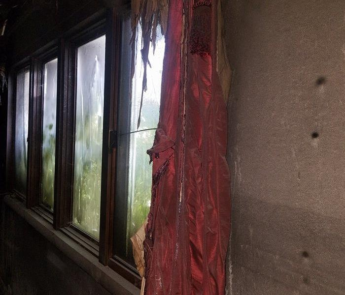 Burnt and soot covered windows and curtain in a house fire.