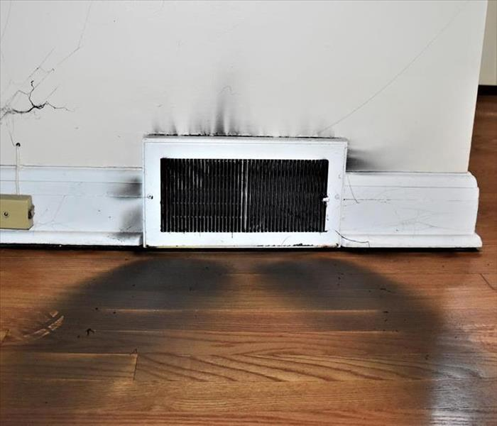 Air vent with smoke damage on the floor in front of it