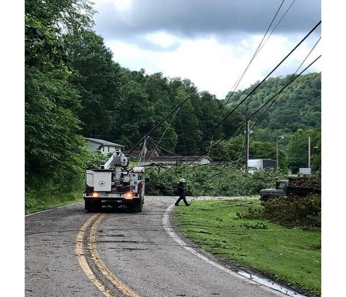 Power company truck and worker repairing power lines after tornado on rural road