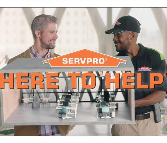 A Servpro technician and a customer standing in an office with the words Here To Help across the screen.