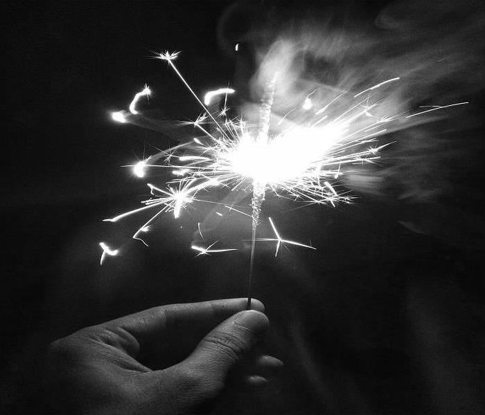 Black and White photo of a hand holding a sparkler.